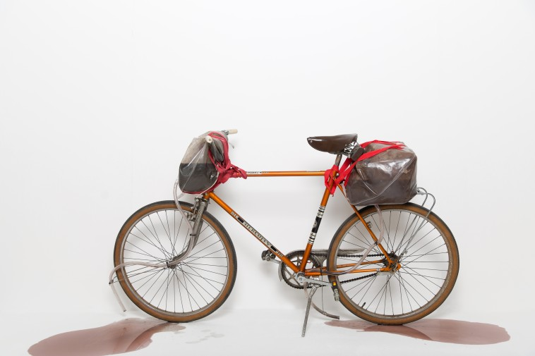 "Bastian Hoffmann, How to prepare a bike that cycles everyday in mud (Skulptur), aus der Tutorial Clip-Serie ""Today I want to show you..."", 2011 – fortlaufend, Fahrrad, Kanister, Schläuche, Spanngurte, Wasser, Erde"
